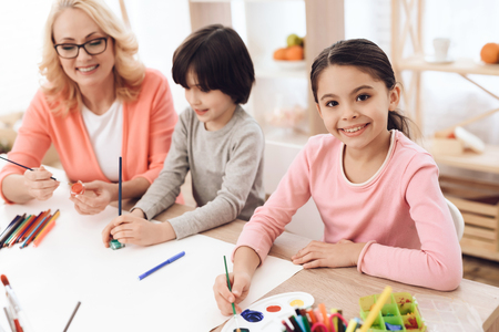 Beautiful elderly woman teaches children to draw. Children draw with paints. Drawing with paints. Little children draw. Painting.