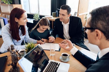 Anwalt zeigt Mutter, wo sie Dokumente unterschreiben muss, während kleine Tochter und Ehemann daneben sitzen. Familie im Büro des Familienanwalts.