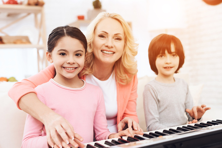 Beautiful elderly woman teaches small grandchildren to play synthesizer. Young grandmother plays piano for her grandchildren.
