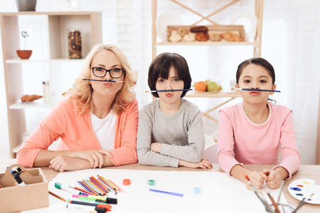 Young grandmother, along with her grandchildren, make faces with help of brushes. Little children draw. Drawing lessons. Courses of fine arts. 写真素材