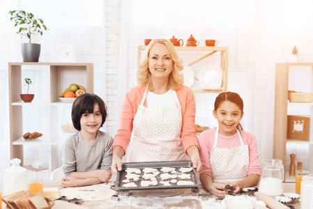 Baking cookies. Beautiful grandmother with her grandchildren bake cookies in kitchen. Grandson and granddaughter together with happy grandmother are engaged in cooking in kitchen. Standard-Bild - 97681100