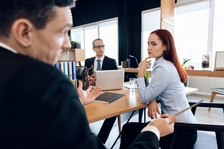 Frustrated red-haired girl looks at adult man who spreads her hands in divorce office. Attorney in business suit is sitting at office table, listening to discussion of divorcing couple.