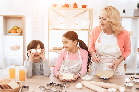 Young grandmother and granddaughter are laughing at little boy who makes face. Grandmother with her grandchildren cooks pastries in kitchen.