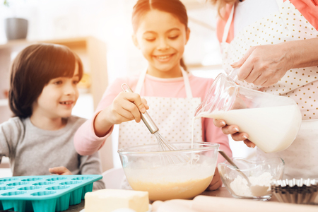 Happy boy looks at little girl who is beating eggs in bowl, where beautiful grandmother pours milk from jug. Grandmother teaches grandchildren to cook. Stock Photo