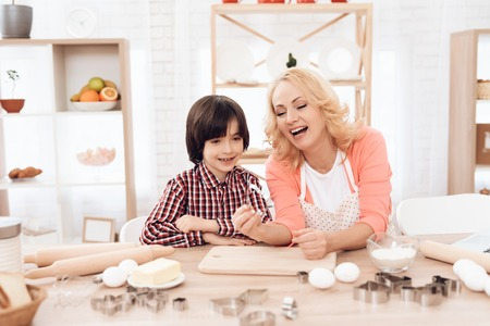 Young joyful grandmother, holding baking dish in her hand, and grandson in plaid shirt are sitting in kitchen. Grandmother teaches grandson to cook. Grandmother with her grandson cooks pastries. Stock Photo