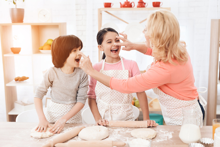Attractive grandmother smeared with flour nose of a joyful grandson and granddaughter in kitchen. Baking cookies. Beautiful grandmother with her grandchildren bake cookies in kitchen. Stok Fotoğraf