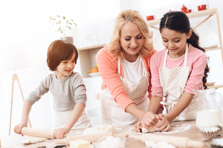 Happy grandmother together with little happy grandchildren knead dough for cookies in kitchen. Grandmother with her grandchildren cooks pastries in kitchen. Baking cookies. Stock Photo - 97680969