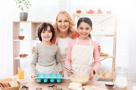 Grandmother with her grandchildren cooks pastries in kitchen. Baking cookies. Grandson and granddaughter together with happy grandmother are engaged in cooking in kitchen.