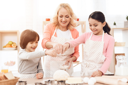 Young beautiful grandmother, along with small happy grandchildren, pours flour on dough in kitchen. Grandson and granddaughter together with happy grandmother are engaged in cooking in kitchen. Imagens