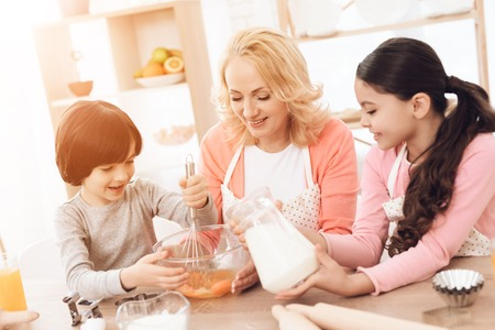 Small smiling boy is whipping eggs in bowl with his sister and young grandmother. Happy little girl pours milk into bowl with eggs.