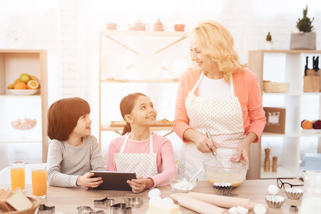 Young grandmother cooks in kitchen with her grandchildren looking at tablet. Grandmother with her grandchildren cooks pastries in kitchen. Stock Photo