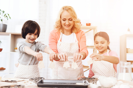 Young grandmother lays biscuit pieces for deco in kitchen. Baking cookies. Grandchildren help grandma to cook pastries in kitchen. Stock Photo