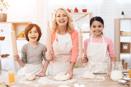 Young happy grandmother together with little happy grandchildren knead dough for cookies in kitchen. Grandmother with her grandchildren cooks pastries in kitchen. Baking cookies.