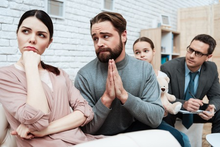Bearded man asks for forgiveness from frustrated woman in office of family psychologist. Couple consults at family psychologists reception. Family psychotherapy concept.