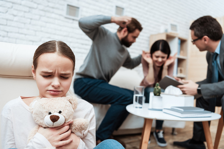Frightenedgirl with teddy bear in hands avoids scandal of parents in psychiatrists office. Brutal treatment of woman in family. Attendance to family psychiatrist. Family psychotherapy concept.