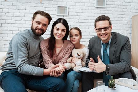楽しい家族は家族心理学者事務所のソワに座っています。セラピーセッション後の家族。心理学者への3人の家族の訪問。