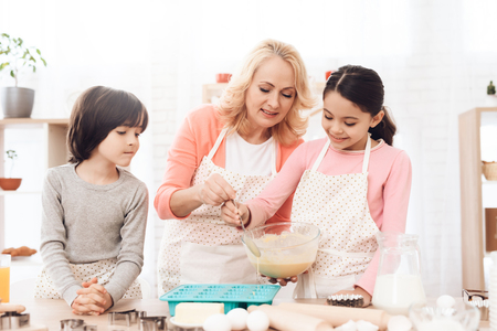 Small grandson watches as grandmother helps her granddaughter pour mixture into baking molds. Beautiful grandmother with her grandchildren bake cookies in kitchen. Reklamní fotografie - 97680793