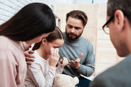 Young couple came with daughter to reception of child psychologist. Psychological help to children. Parents calm small daughter in office of psychotherapist. 스톡 콘텐츠