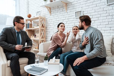 Adult male with woman quarrels near little girl who closes ears in office of family psychologist. Adult couple with small daughter discuss problems in family at psychologist.