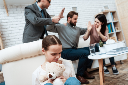 Little girl with teddy bear in hands avoids scandal of parents in psychiatrists office. Brutal treatment of woman in family. Attendance to family psychiatrist. Family psychotherapy concept.