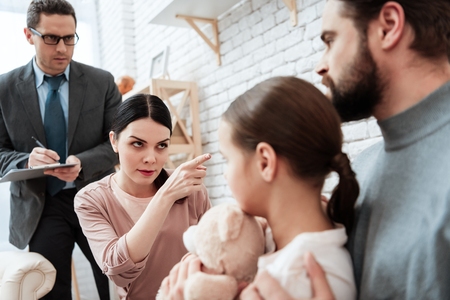 Young woman asks bearded man to leave her and daughter pointing to exit at psychologists office. Discussion of family problems in office of psychologist. Stock Photo