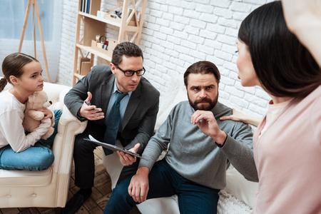 攻撃的な若い女性は、心理学者とオフィスで成人男性を打とうとします。心理学者は若い両親の対立を解決しようとしている。家族精神科医への出席。 写真素材 - 97680676