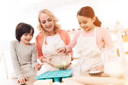 Small grandson watches as grandmother helps her granddaughter pour mixture into baking molds. Beautiful grandmother with her grandchildren bake cookies in kitchen. Reklamní fotografie
