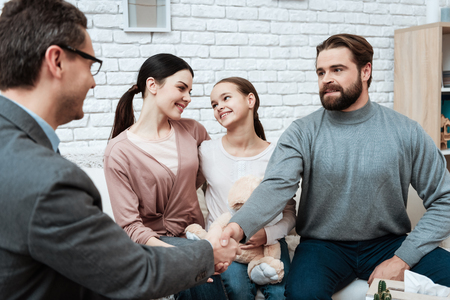 Adult man shakes hands with family psychologist who helped solve problem. Family of three visit to psychologist. Family at reception with family psychologist. Stockfoto