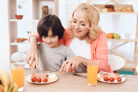 Cute elderly woman helps little boy to cut sausage on plate. Beautiful grandmother helps her grandchild to eat. Little boy is having dinner in kitchen with his grandmother.