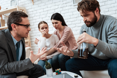 Adult bearded father, holding bottle of whiskey, sits with family at reception of psychologist. Family at reception with family psychologist. Family psychotherapy concept. Stock Photo - 97680560