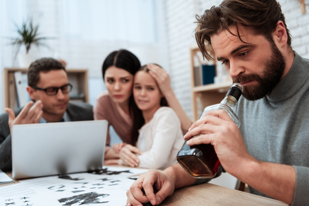 Bearded father is alcoholic with frustrated wife and daughter at psychologist's reception. Discussion of family problems in office of psychologist. Psychological help for family. Stock Photo - 97680434