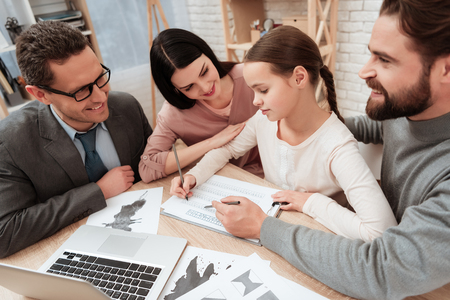 Little girl fills psychological test with family at psychologists reception. Visit to family psychologist. Attendance to family psychologist.