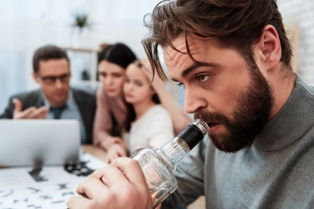 Close up. Bearded man drink alcohol with family at psychologist office. Problem of father of alcoholic in family. Family of three visit to psychologist.