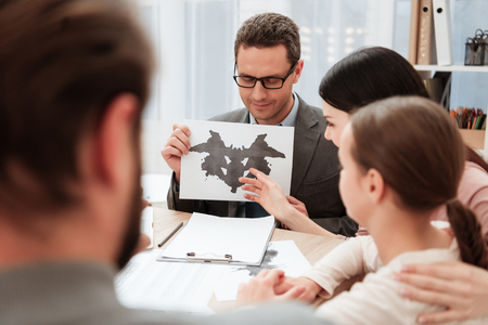 Adult psychologist shows cards with Rorschach spots to family sitting in office. Family of three visit to psychologist. Family psychotherapy concept. Stock Photo