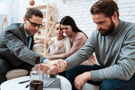 Close up. Confident man grabs fathers hand, which reaches for alcohol. Family in background. Family of three visit to psychologist. Problem of father of alcoholic in family. Stock Photo