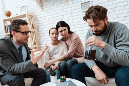 Adult bearded father, holding bottle of whiskey, sits with family at reception of psychologist. Family at appointment with family psychologist. Family psychotherapy concept. Stock Photo - 97680449