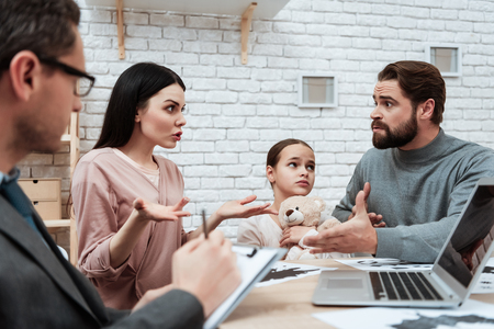 Adult couple with small daughter discuss problems in family at psychologist. Family of three visit to psychologist. Family psychotherapy concept. Stock Photo