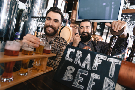 Happy bearded men test beer of different styles in beer samplers in brewery of craft beer. Brewer master checks quality of freshly tapped beer from brewery.