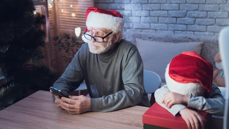 Grandfather and grandson in Santa Clauss hats at table at night at home. Granddad is on phone, boy is sleeping. Stock Photo