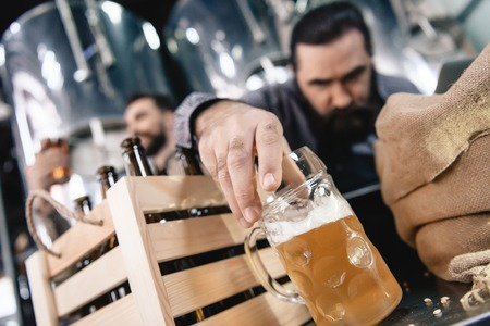 Bearded brewer in apron takes glass of light beer. Brewer is studying density of beer in tumbler. Process of beer manufacturing. Brewing. Brewery. Beer crafting.