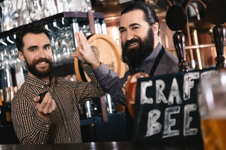 Cheerful bearded men give five to each other, smoking pipes in brewery of craft beer. Smoking tobacco using tube. Banco de Imagens