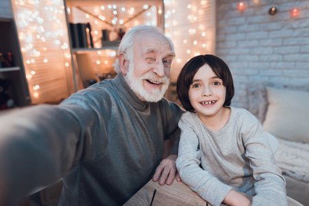 Grandfather and grandson are taking selfie at table at night at home. Stock Photo