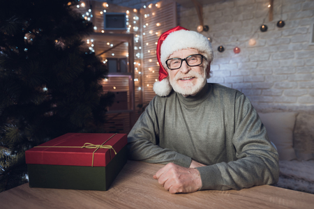 Grandfather is sitting near Cristmas tree in Santa Claus's hat at table at night at home.