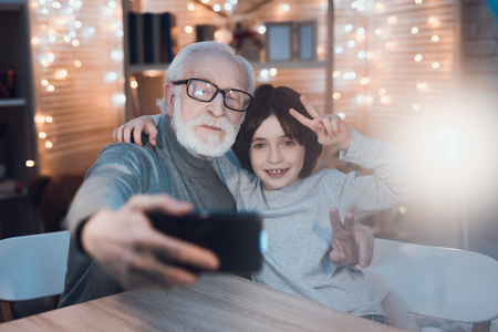 Grandfather and grandson are taking selfie on phone at table at night at home.