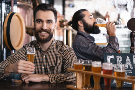 Two bearded men taste a beer of different styles in beer samplers in brewery of craft beer. Brewing. Brewery. Beer crafting.