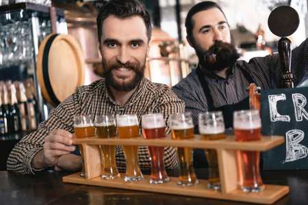 Two bearded men test beer of different styles in beer samplers in brewery of craft beer. Brewer master checks quality of freshly tapped beer from brewery. Reklamní fotografie