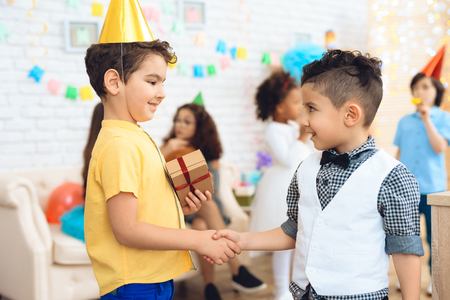 Joyful boy in birthday hat gives a gift to little birthday boy. Gift time. Birthday concept. Festive mood concept. Little boy congratulates on birthday.