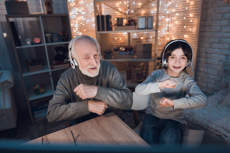 Grandfather and grandson are listening to music in headphones at table at night at home. Banco de Imagens - 98309137
