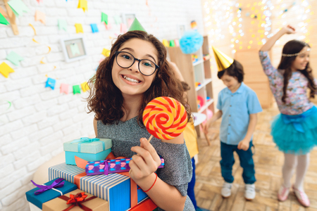 Beautiful girl with bunch of presents is holding colored lollipop in hand at her birthday. Happy birthday party. Children's fun concept.