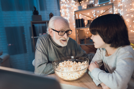 Grandfather and grandson are watching movie with popcorn at table at night at home. Standard-Bild - 103258115
